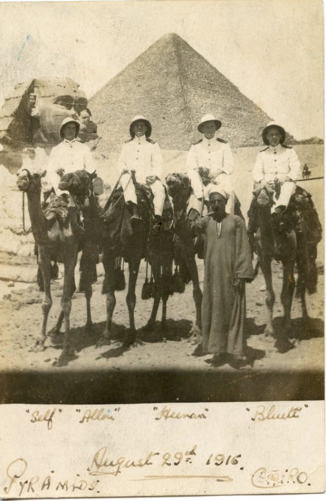 Four men in white naval uniform on camels in front of pyramids at Cairo.One man is Joseph Alfred Heenan.